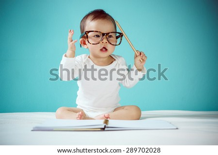 Cute Asian baby girl sitting on stomach on bed, studio shot - stock photo