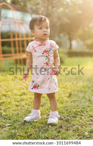 Cute asian baby girl with Chinese dress play in playground