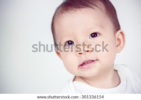 Cute asian baby laughing on white background, studio shot (soft focus on the eyes)