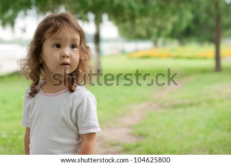 Cute asian baby outdoors at green background, portrait