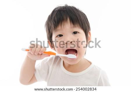Cute asian bay brushing teeth on white background isolated - stock photo