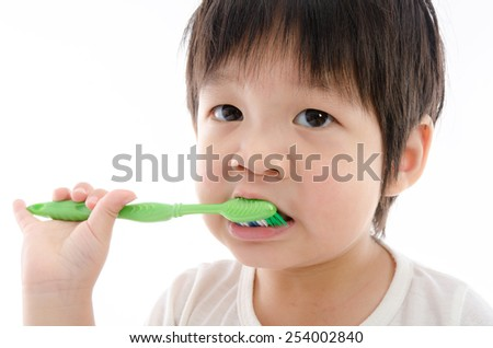 Cute asian bay brushing teeth on white background isolated with copy space