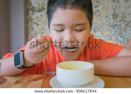 Cute Asian boy eating mushroom soup.