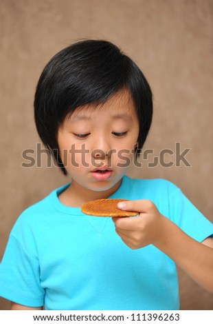 Cute Asian boy enjoying a cookie