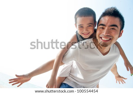 Cute asian boy flying on father - stock photo