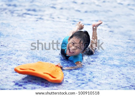 Cute Asian boy having fun at swimming pool during summer time - stock photo