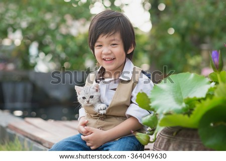 Cute Asian boy  holding american short hair  kitten with sunshine in the park,vintage filter - stock photo