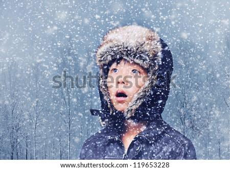 Cute Asian boy looking surprised in winter snowfall - stock photo