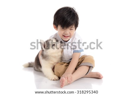 Cute asian boy sitting with siberian husky puppy on white background isolated - stock photo