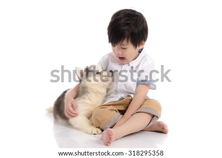 Cute asian boy sitting with siberian husky puppy on white background isolated