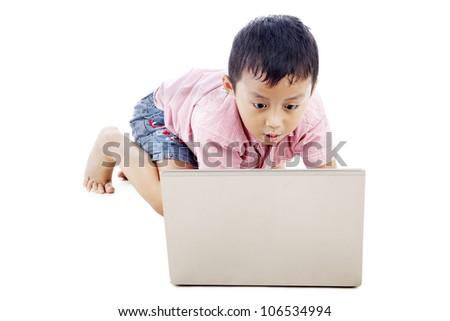 Cute asian boy using laptop computer seriously. shot in studio - stock photo