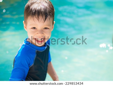 Cute Asian Caucasian mixed race toddler happily playing in a pool outside in the summer sun