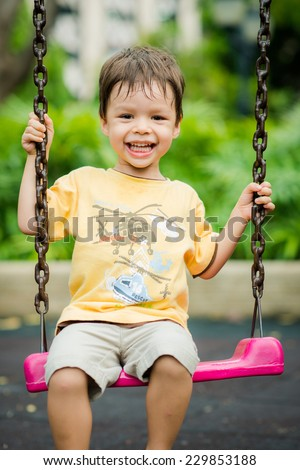 Cute Asian Caucasian mixed race toddler happily playing on a swing in a playground outside in the summer sun - stock photo