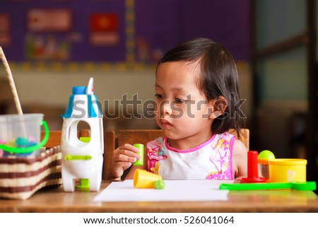 Cute asian child girl playing toys on the wood table in classroom.Selective Focus