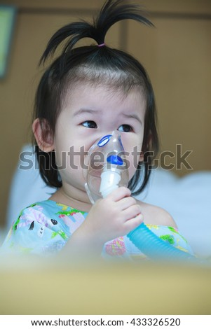 Cute asian child holds a mask vapor inhaler for treatment of asthma on sickbed in hospital. Breathing through a steam nebulizer. Concept of inhalation therapy apparatus. - stock photo