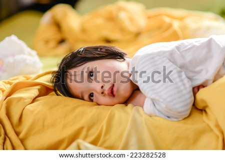 Cute Asian child lying on bed. - stock photo