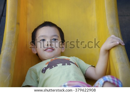 cute asian child playing at playground alone