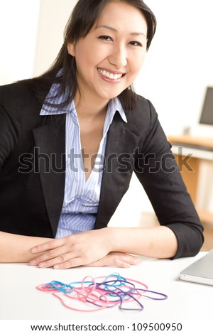 Cute Asian female having fun at work with rubber bands wearing a black suit and blue shirt. - stock photo