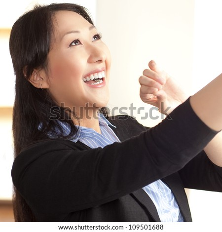Cute Asian female having fun at work with rubber bands wearing a black suit and blue shirt.