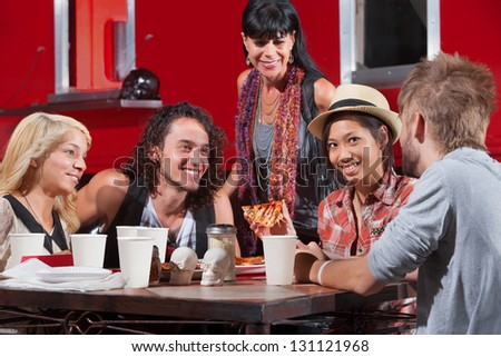 Cute Asian female with hipster friends eating pizza outside - stock photo