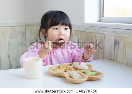 cute asian girl eating lunch at kindergarten.