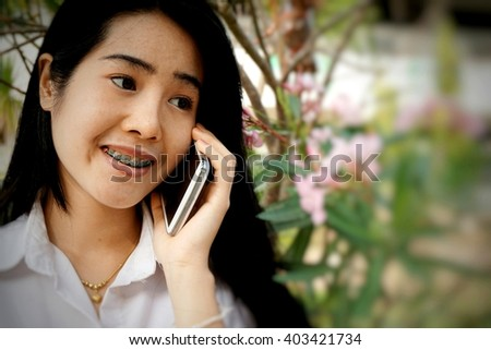 cute Asian girl having fun talking on smart phone in soft tone, technology concept background  - stock photo