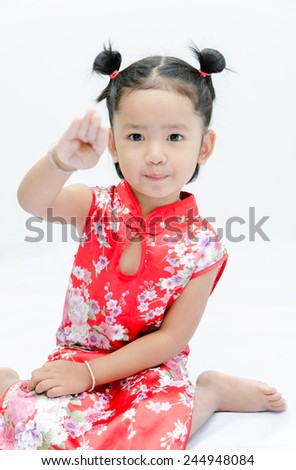 Cute asian girl in red chinese dress on the white background