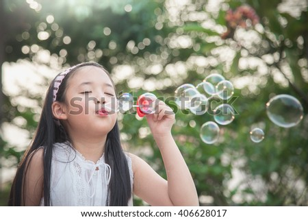 Cute asian girl is blowing a soap bubbles,vintage filter