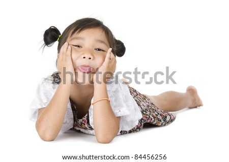 cute Asian girl laying on the floor, sticking her tongue out over white background - stock photo