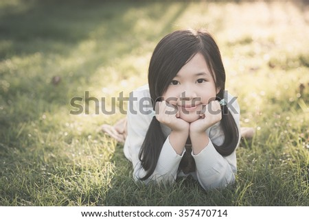 Cute asian girl lying on grass,vintage filter - stock photo