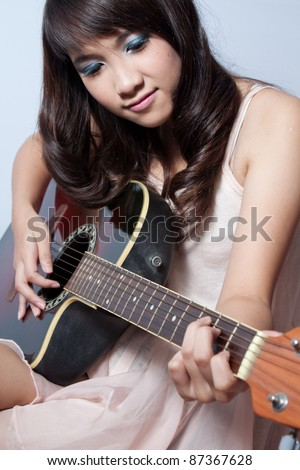 Cute asian girl playing guitar