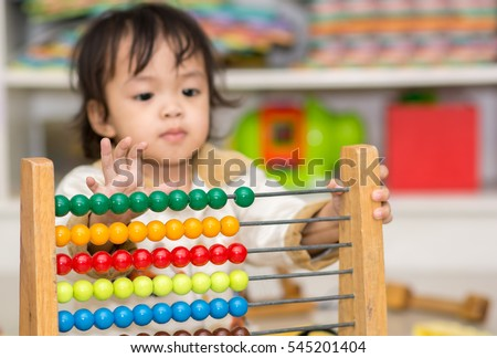 Cute Asian girl Playing with an Abacus Learning to Count ,selective focus on colorful Abacus