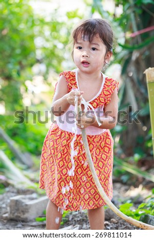 Cute Asian girl smiling and playing in Songkran festival