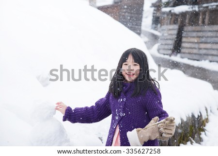 Cute asian girl smiling outdoors in snow on cold winter day - stock photo