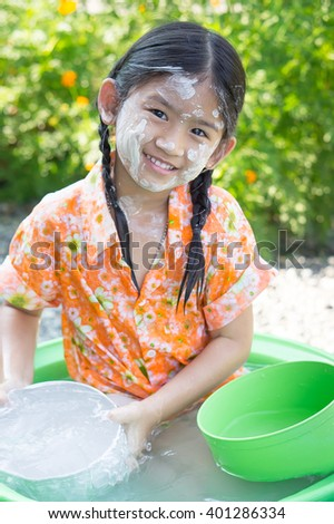 Cute Asian girl smiling when she playing and holding water cup in her little plastic basin on Songkran fastival Thailand.Songkran ceremony, Thai New Year. - stock photo