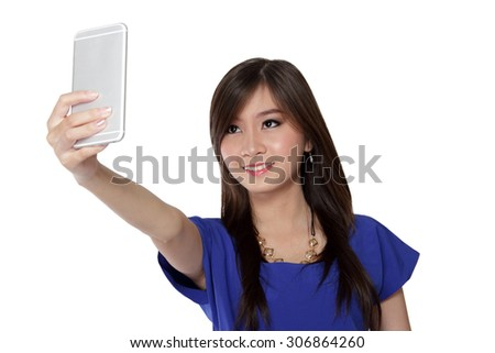 Cute Asian girl taking a picture using smartphone and smiling, isolated on white background - stock photo