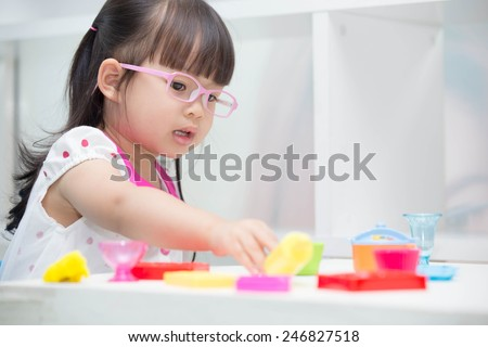 Cute Asian girl wearing glasses playing toys happily. - stock photo