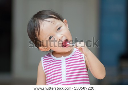 Cute asian girl with lollipop