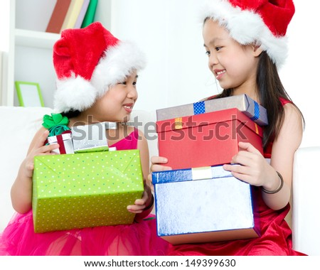 Cute asian girls carrying christmas gift boxes - stock photo
