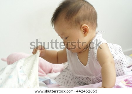 Cute Asian infant baby finding something hidden under a blanket.