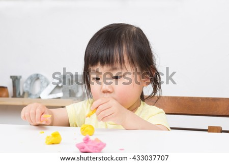 cute asian kid playing clay