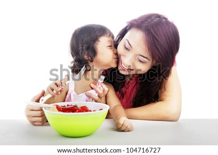 Cute asian little girl with fruit salad kissing her mother