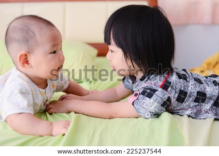 Cute Asian sisters playing on bed. - stock photo