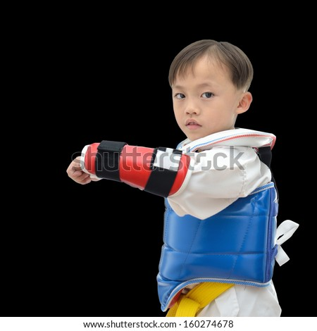 Cute asian teakwondo boy on black background. - stock photo