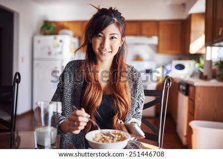 cute asian teen girl eating breakfast in kitchen with smart phone - stock photo