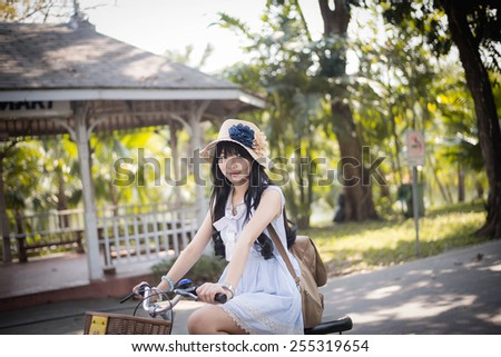 Cute Asian Thai girl in vintage clothing is riding a bicycle, in the sunny summer park shade  - stock photo