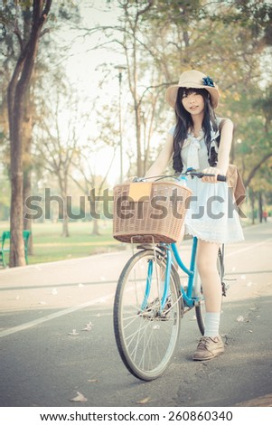 Cute Asian Thai girl in vintage clothing is standing with her bicycle, in the sunny summer park. - stock photo