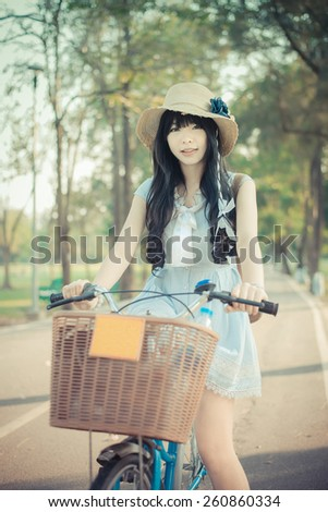 Cute Asian Thai girl in vintage clothing is standing with her bicycle, in the sunny summer park in soft vintage color - stock photo