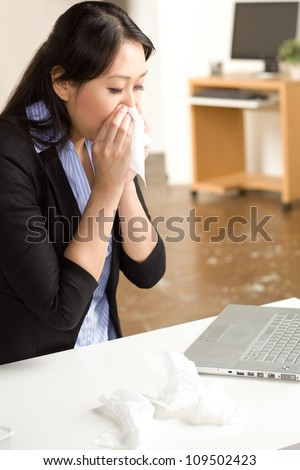 Cute Asian woman in an office setting with a cold wearing a black suit and blue shirt
