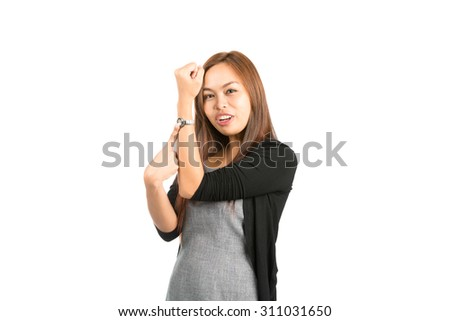 Cute Asian woman in black sweater, light brown hair holding up wrist pointing at wristwatch indicating to hurry, not enough time, late. Thai national of Chinese origin - stock photo